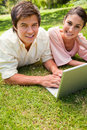 Two friends looking towards the side while using a laptop Royalty Free Stock Image