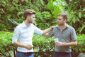 Two friends men talking standing in a garden. Royalty Free Stock Photo