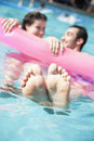 Two friends in a pool holding onto an inflatable raft with feet sticking out of the water Royalty Free Stock Photo