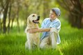 Two friends portrait of cute lad embracing his white labrador and looking at it Stock Photography