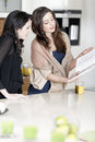 Two friends reading recipes Royalty Free Stock Photo