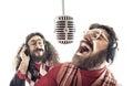 Two friends singing a karaoke Royalty Free Stock Photo