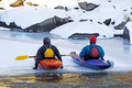 Two Friends Sitting on Ice In Colorful Kayaks Royalty Free Stock Photo