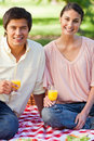 Two friends smiling while holding glasses of juice during a picnic Royalty Free Stock Photo