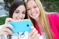 Two friends taking photos with a smartphone outdoor portrait of Royalty Free Stock Images