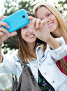 Two friends taking photos with a smartphone outdoor portrait of Royalty Free Stock Photography