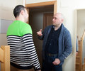 Two friends talking adult men opening door his neighbor Royalty Free Stock Photo