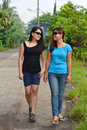 Two friends walking asian female having fun with conversation while in the street Royalty Free Stock Photos