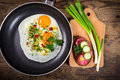 Two frying eggs in pan with sausage sandwich greens on wooden table Stock Photography