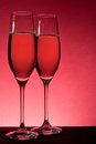 Two full glasses of champagne over red background Royalty Free Stock Photography