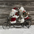 Two funny santa claus on a tandem in hurry for christmas shoppin shopping witty advent decoration december Stock Photo