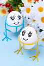 Two funny smiling eggs on stands and flowers for Easter Royalty Free Stock Image