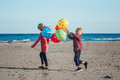 Two funny white Caucasian children kids with colorful bunch of  balloons, playing running on beach on sunset, autumn summer Royalty Free Stock Photo