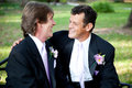 Two gay grooms on wedding day couple celebrating their marriage together outdoors Royalty Free Stock Image