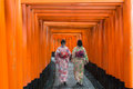 Two geishas among red wooden Tori Gate at Fushimi Inari Shrine i Royalty Free Stock Photo