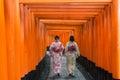 Two geishas among red wooden Tori Gate at Fushimi Inari Shrine i Royalty Free Stock Photo