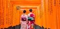 Two geishas among red wooden Tori Gate at Fushimi Inari Shrine in Kyoto, Japan Royalty Free Stock Photo