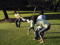 Two generation family playing tug of war on grass in park Stock Photography