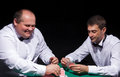 Two gentlemen in white shirts playing cards on black background Stock Photo