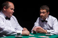 Two gentlemen in white shirts playing cards on black background Royalty Free Stock Photography