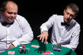 Two gentlemen in white shirts playing cards on black background Royalty Free Stock Images