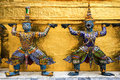 Two giant statue in temple bangkok thailand standing front gold wall background at Royalty Free Stock Photos