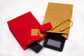 Two gift bags with electronics a red bag a mobile and a gold bag a tablet pc isolated Royalty Free Stock Photography