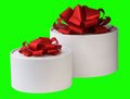 Two gift boxes the image of white round with red tapes is on a green background Stock Photography