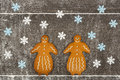 Two gingerbread ladies together on floury table with snowflakes and snowy environment from the flour a dark wooden Stock Photo