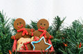 Two gingerbread men in cart in greens Royalty Free Stock Images