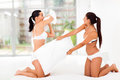 Two girl friends having pillow fight bedroom Royalty Free Stock Photos