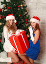 Two girlfriends with a gift near the christmas tree Stock Images