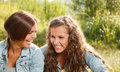 Two girlfriends in jeans wear outdoors sitting laughing Royalty Free Stock Photo