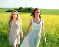 Two girlfriends in long dresses together outdoors portrait the summer field Stock Image