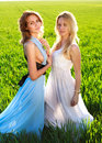 Two girlfriends in long dresses, together outdoors Royalty Free Stock Photo