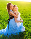 Two girlfriends in long dresses together outdoors portrait the summer field Stock Photo