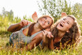 Two girlfriends lying down on grass in t shirts laughing having good time Royalty Free Stock Image