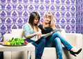 Two girlfriends sat down sofa Stock Images