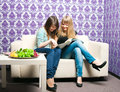 Two girlfriends sat down sofa Royalty Free Stock Image