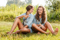 Two girlfriends sitting on grass in jeans wear having fun Stock Photo