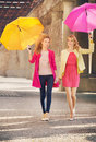 Two girlfriends walking during windy day cheerful Royalty Free Stock Images