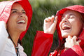 Two girlfriends wearing raincoat enjoying the rain Royalty Free Stock Photo