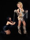 Two girls in barbarian and cat costumes eoung beautiful women on black background Royalty Free Stock Photo