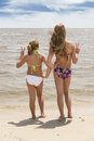 Two girls at beach looking at water are sisters Stock Photography