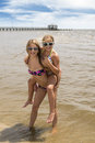 Two girls at beach playing in water and surf Royalty Free Stock Photo