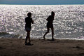 Two girls on beach silhouette of having fun at sunset Royalty Free Stock Photography