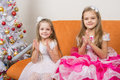 Two girls in beautiful dresses guessing gifts for new year Royalty Free Stock Photo
