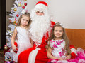 Two girls in beautiful dresses hug Santa Claus sitting on the couch, one of them a little displeased Royalty Free Stock Photo