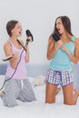 Two girls on bed singing into their hairbrushes Royalty Free Stock Photo