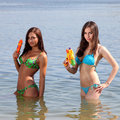 Two girls in bikini play with a water guns Royalty Free Stock Images